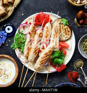 Chicken kebab, Tavuk sish kebab with parsley, grilled eggplant, red pepper and yogurt sauce on dark background. Top view, square crop - Stock Photo