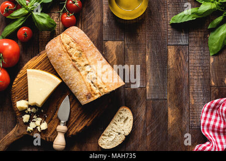 Italian food on rustic wood background, top view. Parmesan cheese, ciabatta, bruschetta, basil, olive oil and tomatoes. Italian cuisine - Stock Photo