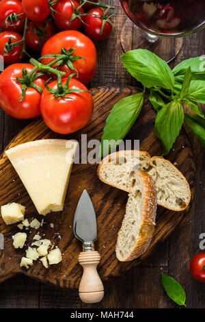 Parmesan cheese, ciabatta, basil, fresh tomatoes and glass of red wine. Italian food, italian cuisine. Top view