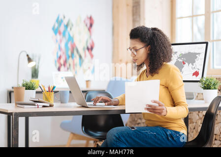 Concentrated young businesswoman working on her laptop - Stock Photo
