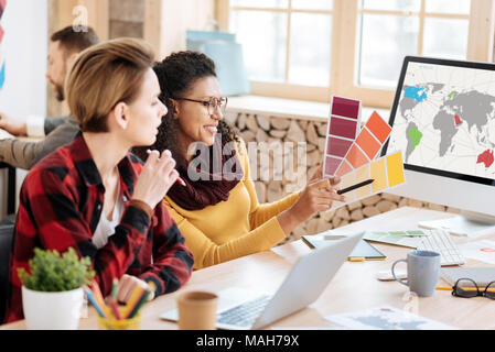 Content woman discussing work with her co-worker - Stock Photo
