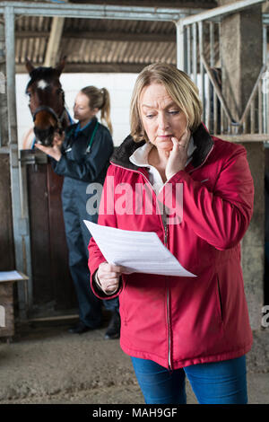 Worried Female Horse Owner Looking At Bill From Vet - Stock Photo