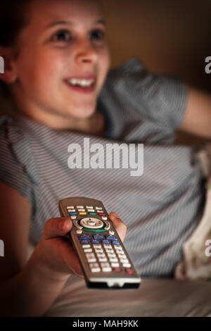 Young Girl  Lying In Bed  Watching TV At Night - Stock Photo