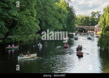 People on holiday, relaxing & boating in rowing boats on River Nidd under blue sky - scenic sunny summer view by bridge, Knaresborough, England, UK. - Stock Photo