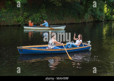 4 people boating, relaxing & having fun in 2 rowing boats (1 young woman in boat is taking selfie) - River Nidd in summer, Knaresborough, England, UK. - Stock Photo