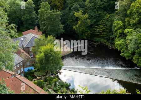 High view of water flowing over weir across River Nidd & historic Castle Mills, an old textile mill converted to homes - Knaresborough, England, UK. - Stock Photo