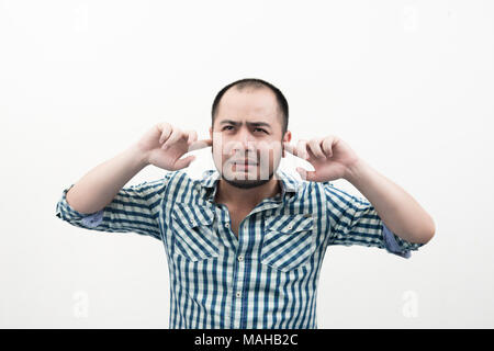 Portrait of young unhappy, stressed man covering his ears, looking up don't want to hear anything isolated white background. - Stock Photo