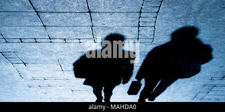 Silhouette shadows of two traveling people walking on city street in the night - Stock Photo