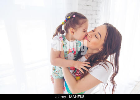 Self portrait of crazy, foolish mother and doughter showing tongue out, kid making selfie on mobile phone over grey background, spending weekend, woman's day together - Stock Photo