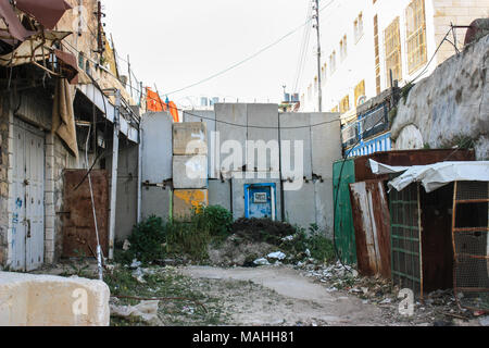 Blocked road exit in the city of Hebron to separate a jewish settlement from a palestinian street. With former shops beeing welded tight - Stock Photo