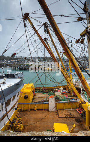 fishing boats and trawlers alongside moored in the cornish fishermans docks at newlyn in cornwall. trawling gear and deep sea trawlers in port newlyn. - Stock Photo