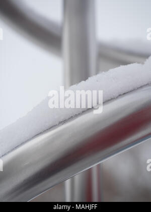 Close up of snow covered metal pipes in an abstract pattern. - Stock Photo