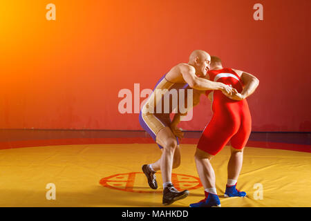 Two greco-roman  wrestlers in red and blue uniform making a suplex wrestling  on a yellow wrestling carpet in the gym - Stock Photo