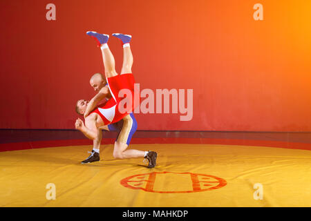 Two greco-roman  wrestlers in red and blue uniform making a   hip throw  on a yellow wrestling carpet in the gym - Stock Photo