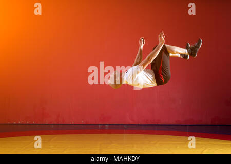 A young athletic man in sportswear makes a somersault in the wrestling hall. Parkour in the gym - Stock Photo