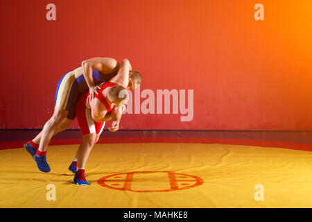 Two greco-roman  wrestlers in red and blue uniform wrestling  on a yellow wrestling carpet in the gym. Young man grappling - Stock Photo