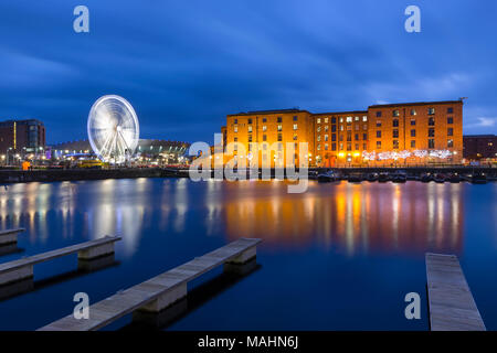 Red brick buildings of the Albert Dock, The Wheel of Liverpool and Liverpool Arena viewed from Salthouse Dock at Night - Stock Photo