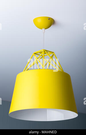 Yellow ceiling lamp in a modern minimalist style. Chandelier photographed close-up - Stock Photo
