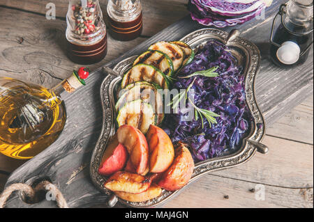 Braised red cabbage with grilled chunks of apples and onions, seasoning with lemon and olive oil on a beautiful dish. - Stock Photo