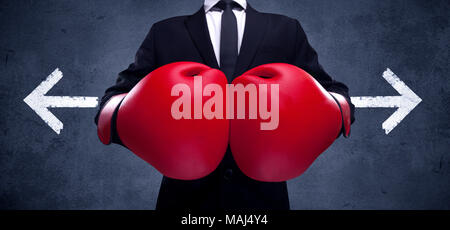 A confident businessman standing with red boxing gloves on his hand in front of arrows pointing in different directions on urban wall background concept. - Stock Photo