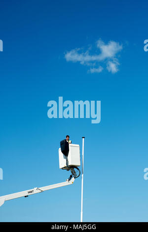 An empty flag pole and  a workman on a cherry picker lift. - Stock Photo