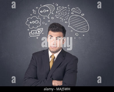 Young businessman with drawn speech bubbles over his head - Stock Photo
