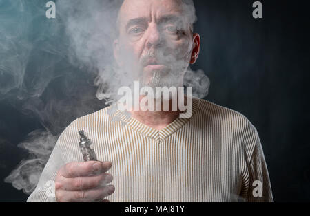 portrait of a man with beard who is vaping - Stock Photo