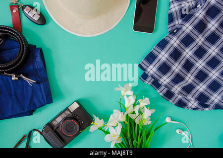 Traveler accessories. Hat, camera, clothing and flowers and phone on the green background. - Stock Photo