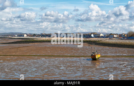 Morecambe Bay Lancashire on the North West Coast of England at low tide showing a fishing boat resting on the sands on a bright sunny afternoon - Stock Photo