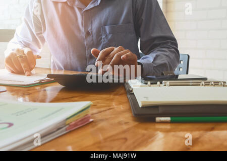Close up Businessman hand using calculator. Professional investor calculate about cost. Finance managers task. - Stock Photo