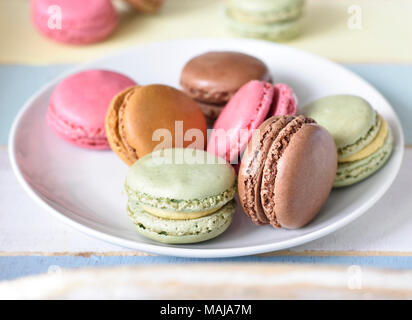 Delicious macaroons or macaron biscuits on a tablet. Coffee break scene with colorful macarons and selective focus. - Stock Photo