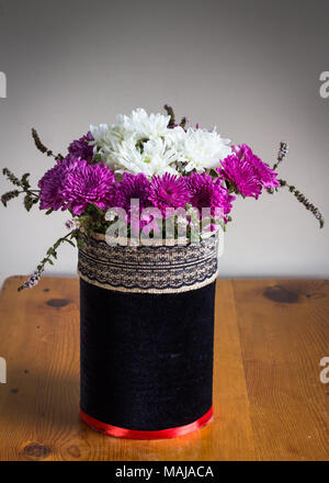 Chrysanthenums in a rustic black velvet covered vase with embroidered ribbon band - Purple and white flower arrangement on wooden table - Stock Photo