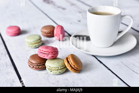 Delicious macaroons or macaron biscuits and coffee cup. Coffee break scene with colorful macarons and white table. - Stock Photo
