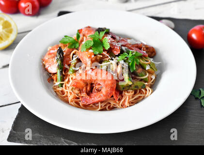 Spaghetti frutti di mare or pasta dish with shrimps and green asparagus and parsley garnish. White plate on a wooden table, healthy eating scene. - Stock Photo