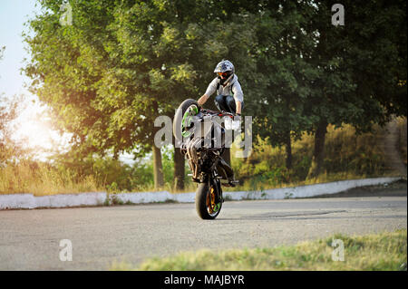Ivano-Frankivsk, Ukraine - 28 August 2015 : Male biker is training in making tricks on sport motorcycle on summer cite street. Green trees on background. Wearing helmet. - Stock Photo