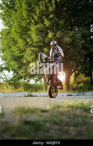 Ivano-Frankivsk, Ukraine - 28 August 2015 : young biker is impressing with his extreme riding skills on city summer streets. Green trees on background. wearing protective helmet. - Stock Photo