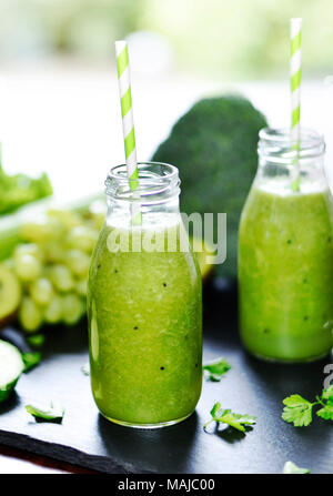 Green smoothie in drinking glasses. Fitness or dieting drink with kiwi, broccoli, lettuce and various ingredients. Healthy drink in a glass bottle. - Stock Photo