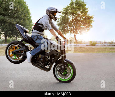 Ivano-Frankivsk, Ukraine - 28 August 2015 : Expressing himself. Talented stunt biker on a riding motorcycle on one wheel. Summer cite street filled with light of sunshine. - Stock Photo