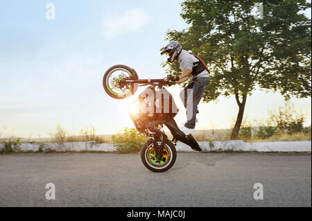 Ivano-Frankivsk, Ukraine - 28 August 2015 : Extreme stunt driver is jumping on his sport motorcycle while riding in extreme way. Summer sunny evening. Adrenaline riding. - Stock Photo