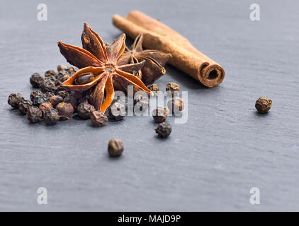Christmas spices on a black background. Christmas or advent baking with dried star anise, cinnamon, peppercorns. - Stock Photo