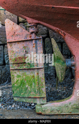 the rudder and propellor on an old fishing boat or trawler high and dry alongside the harbour wall at the cornish fishing port of newlyn in conrnwall. - Stock Photo