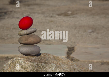 Copy space to right of conceptual background of three stacked river rocks with red nest egg on top in horizontal photograph.  Focus on precarious stac - Stock Photo