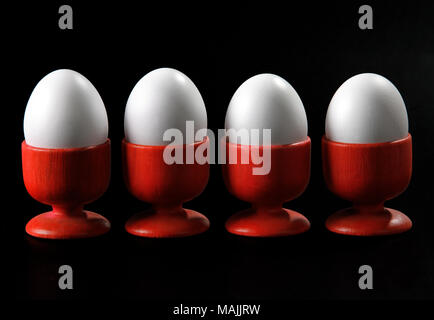 four eggs in red cups on black background - Stock Photo