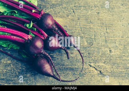 Pile of homegrown organic young beets with green leaves on the table. Fresh harvested beetroots on wooden background with place for text. Rustic style - Stock Photo