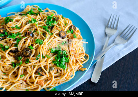 Spaghetti Alla Puttanesca - traditional italian pasta with black olives, tuna, anchovies, capers and parsley. Vegetarian food. Italian cuisine. - Stock Photo