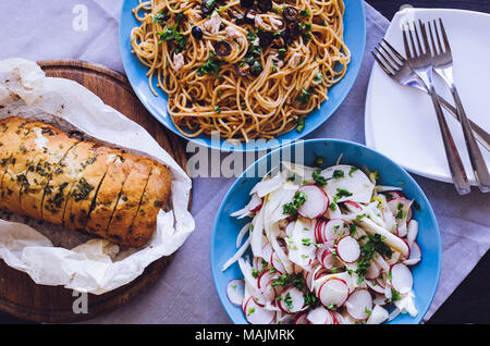 Traditional Italian dinner - Spaghetti Alla Puttanesca pasta with black olives, tuna, anchovies, capers and parsley, vegetable salad and baked ciabatt - Stock Photo