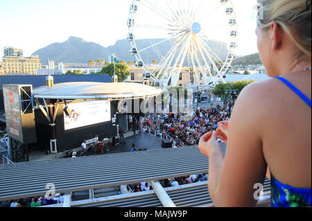 Lady watching Judith Sephuma - South African jazz and Afro-pop singer - live on the V&A waterfront, on a summer's evening, in Cape Town, South Africa - Stock Photo