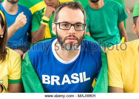 Group of brazilian supporters cheering at stadium. Emotions portrait. Man wearing generic brandless blue t-shirt written 'Brasil' (Brazil in portugues - Stock Photo