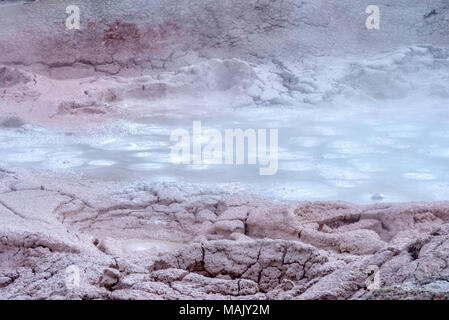 Cracked earth and boiling muddy water with steam rising up off the surface. - Stock Photo
