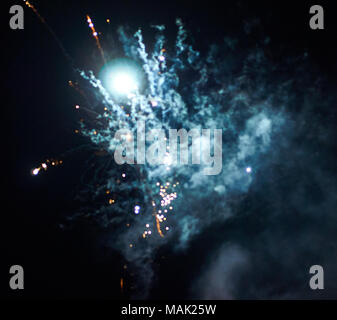 Bright firework rocket before the explosion covered by smoke in the night sky close-up blured background - Stock Photo